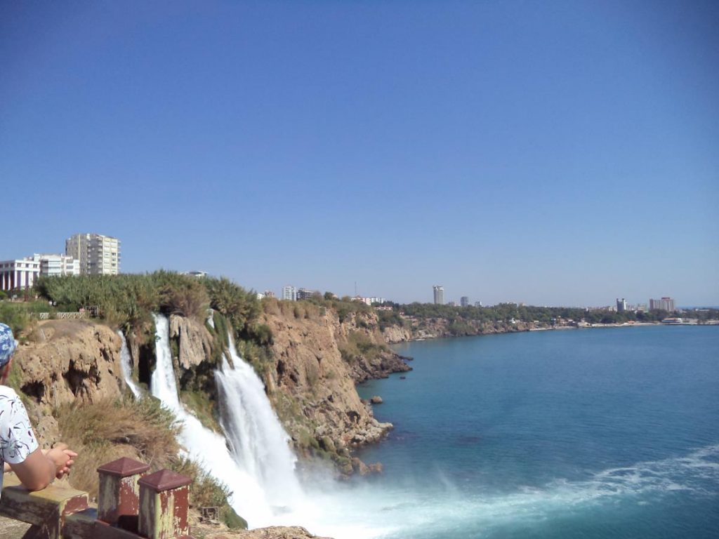 View of Lower Düden Falls from Düden Park. The waters of the Düden River can be seen crashing dramatically over a cliff directly into the Mediterranean Sea. The falls are located on the eastern edge of Antalya, about 5 miles (8.5 km) along the coast from the old centre of the city.