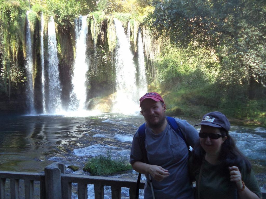 Tony and Tatiana in front of the Upper Düden Falls. Several separate cascades of water pouring over a vegetation covered cliff into a pool.
