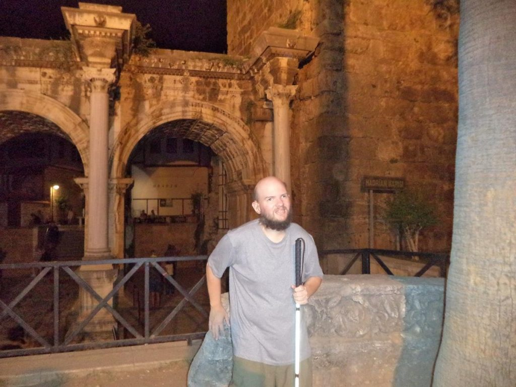 Tony in front of a large carved block of stone, likely of Roman origin, with Hadrian's Gate behind.