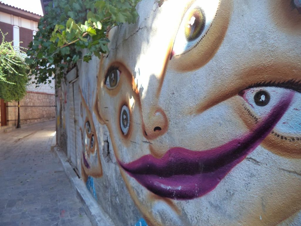A mural on a wall depicting a stylised face with four eyes and large purple lips. On a quiet narrow street in the old city.