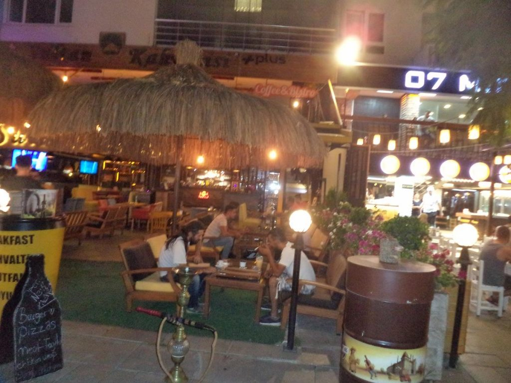 A row of cafés and restaurants with extensive outdoor seating. A shisha water-pipe on the pavement in front.