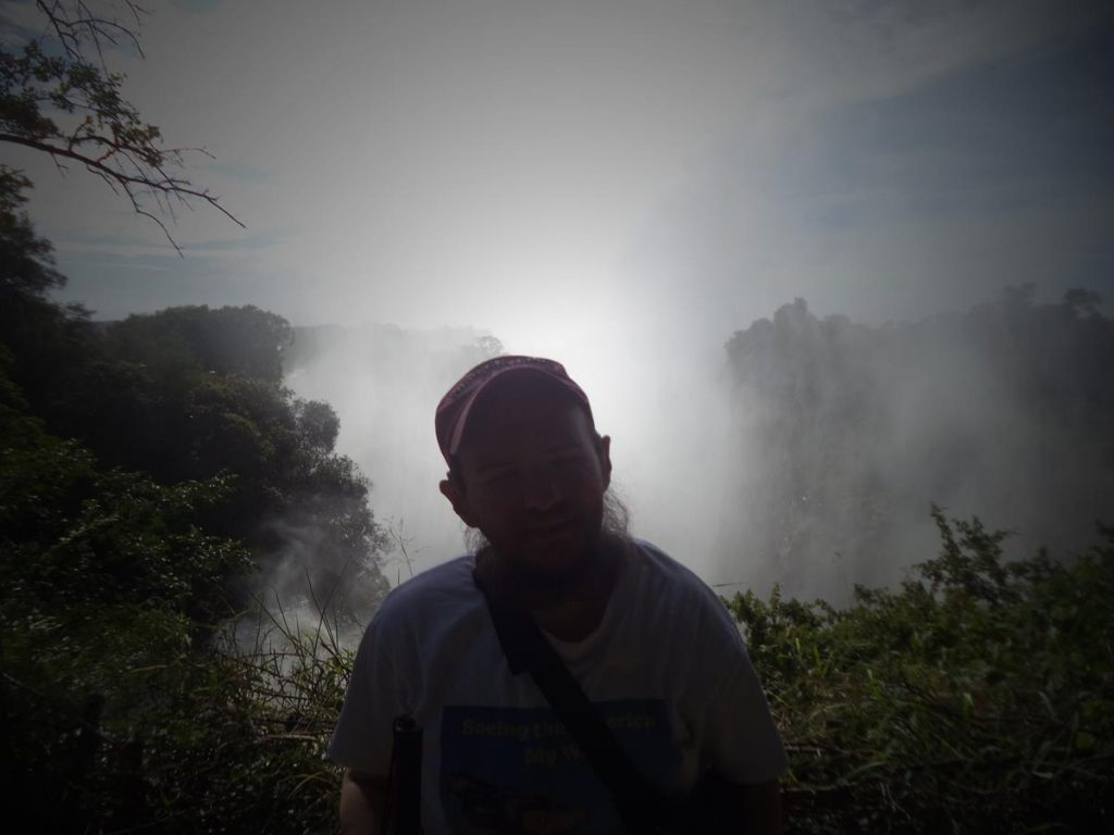 Tony with the gorge behind. A halo of the sun reflected in the mist.  The mist is generated by the crashing water. Here the waterfalls are  difficult to distinguish in the misty haze.