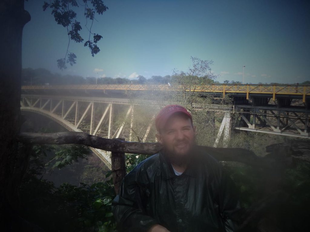 Tony with Victoria Falls Bridge behind. This bridge crosses the  Zambezi at the Second Gorge. The centre of the river forms the border between Zimbabwe and Zambia. The bridge can be seen from viewpoint 16,  the final viewpoint on the Zimbabwean side of the falls.