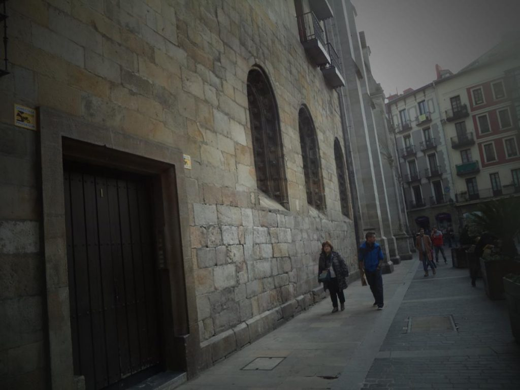 Entering the small medieval square of Plaza de Santiago. The stone wall on the left is part of Santiago Cathedral's west façade.
