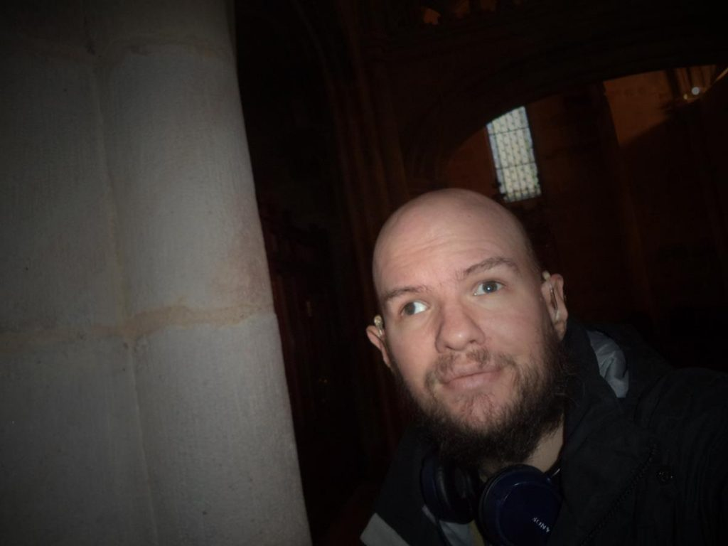 Close-up of Tony next to one of the cathedral's large interior stone columns.