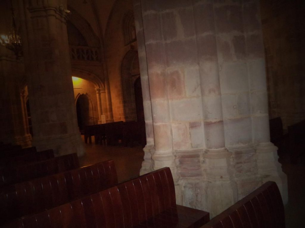 Row of large stone columns down the main aisle of the cathedral.