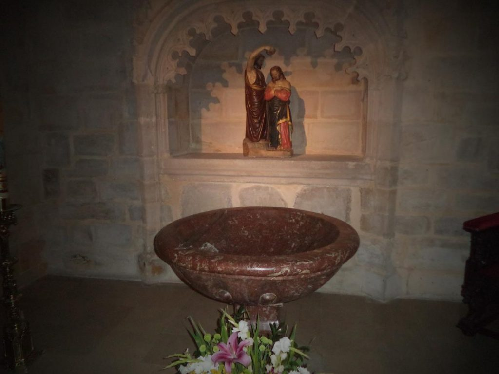 View of the Baptismal Chapel. A large baptismal font made of red limestone in the foreground with a stone altar behind.