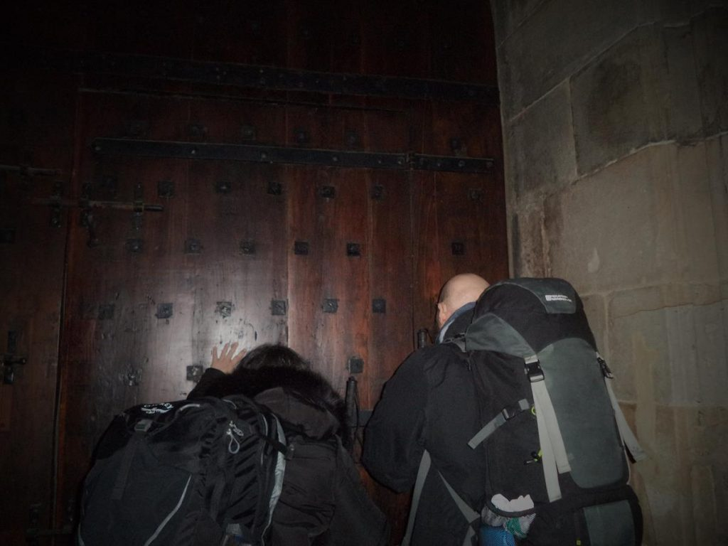 Tony and Tatiana facing towards and touching one of the doors.
