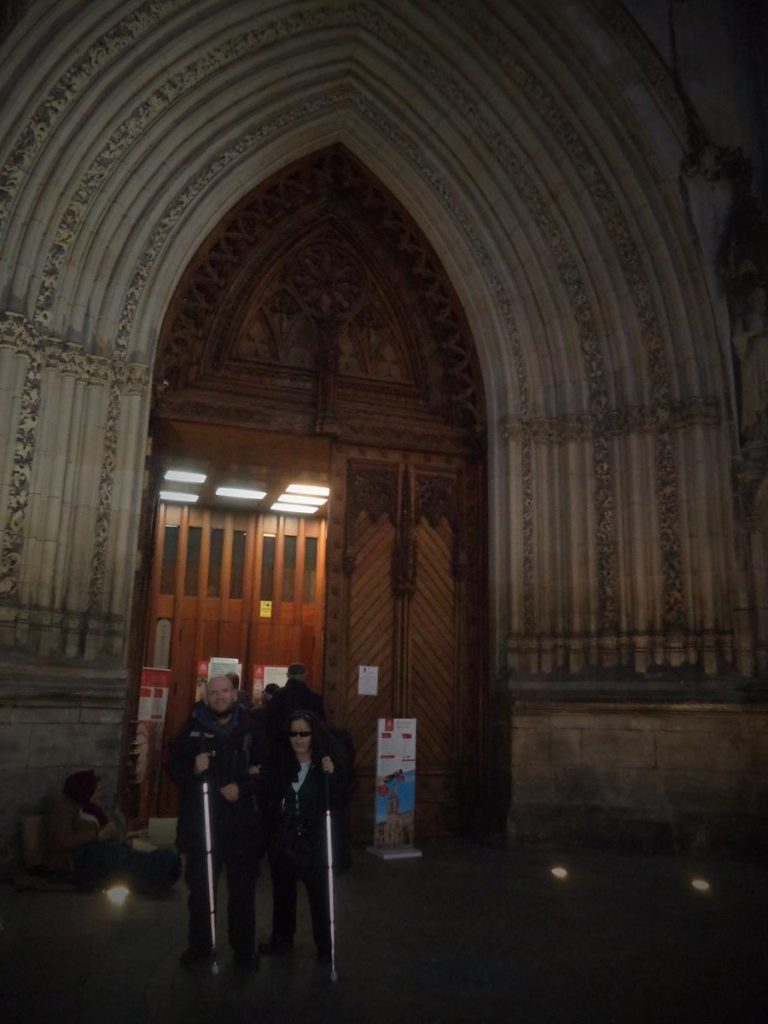 Tatiana and Tony now standing outside the cathedral's main doorway. Lit up in semi-darkness.