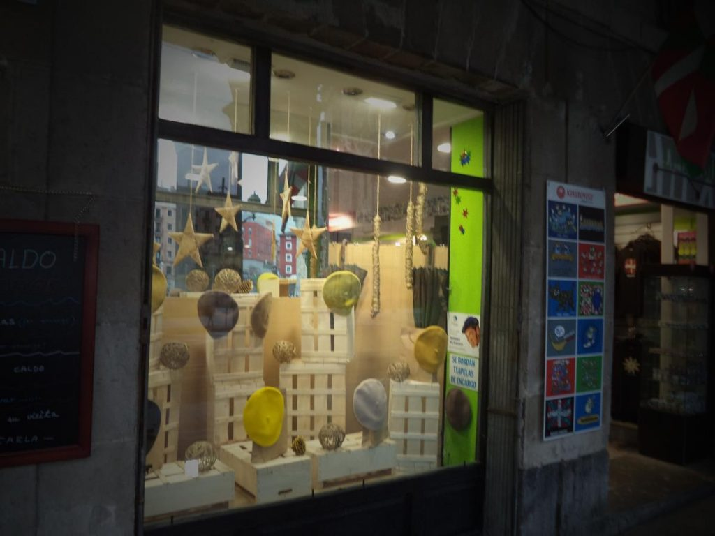 A shop with a display of beret hats in the window.