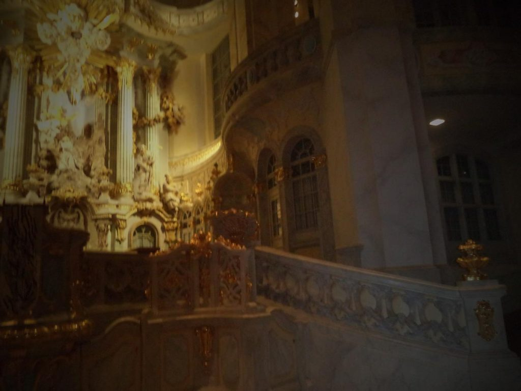 Slightly blurred view of the white and gold main altar containing a relief depiction of Jesus' Agony in the Garden of Gethsemane on the Mount of Olives by Johann Christian Feige. The altar and the surrounding structure were among the remnants left standing, although damaged, following the 1945 bombing.