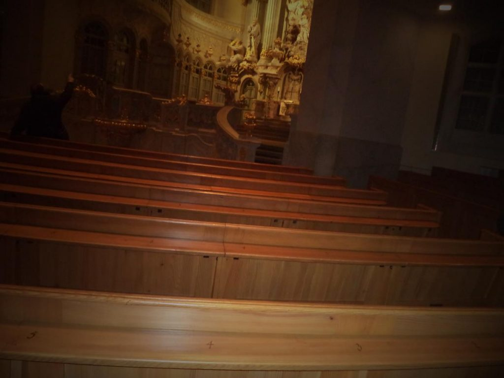 View across rows of pews with the main altar and pulpit part visible beyond.