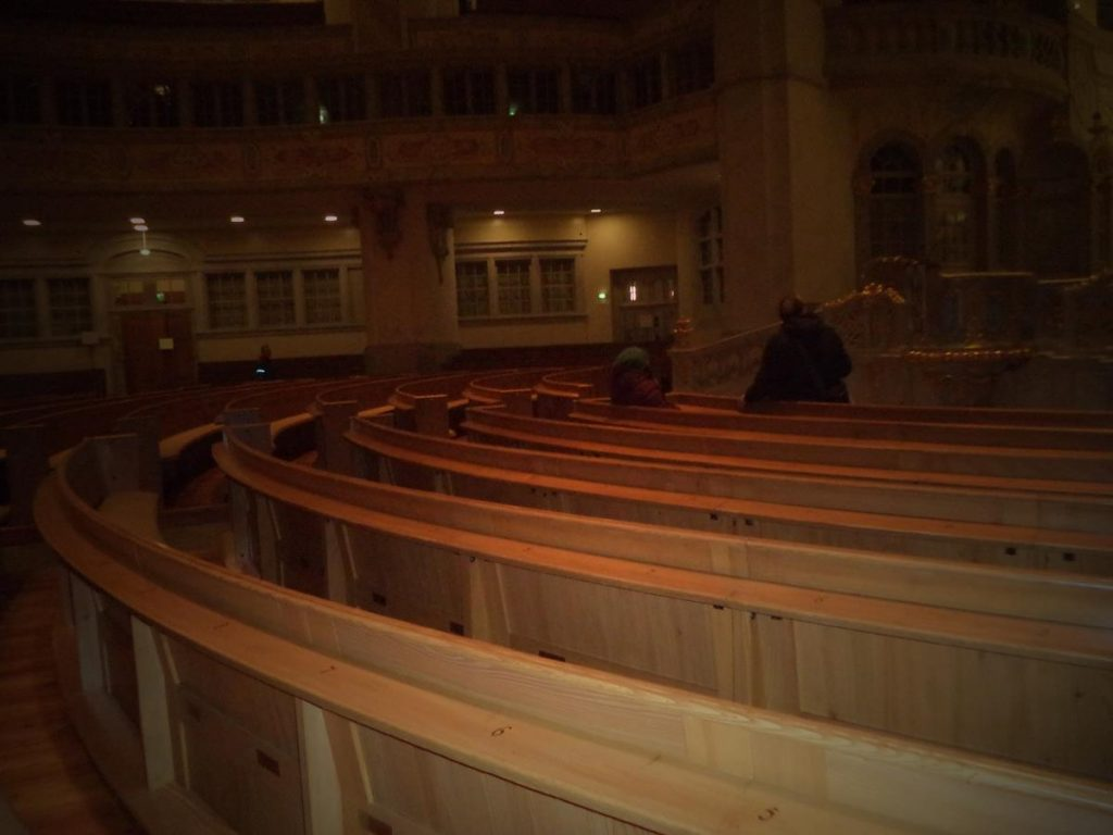 Looking over the pews, showing their arrangement in a semi-circle around the pulpit and altar.