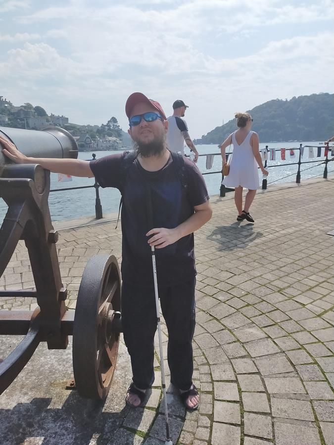 Tony touching an old canon located on the Embankment at Dartmouth. It points into the River Dart estuary, which is visible behind, with Kingswear on the far bank.