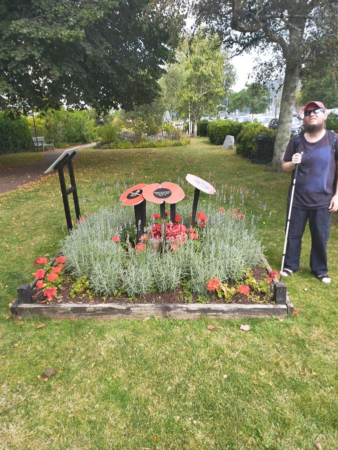 Tony in Dartmouth Community Garden. A small park located next to the river. He is next a memorial flower bed remembering naval cadets killed in World War II.