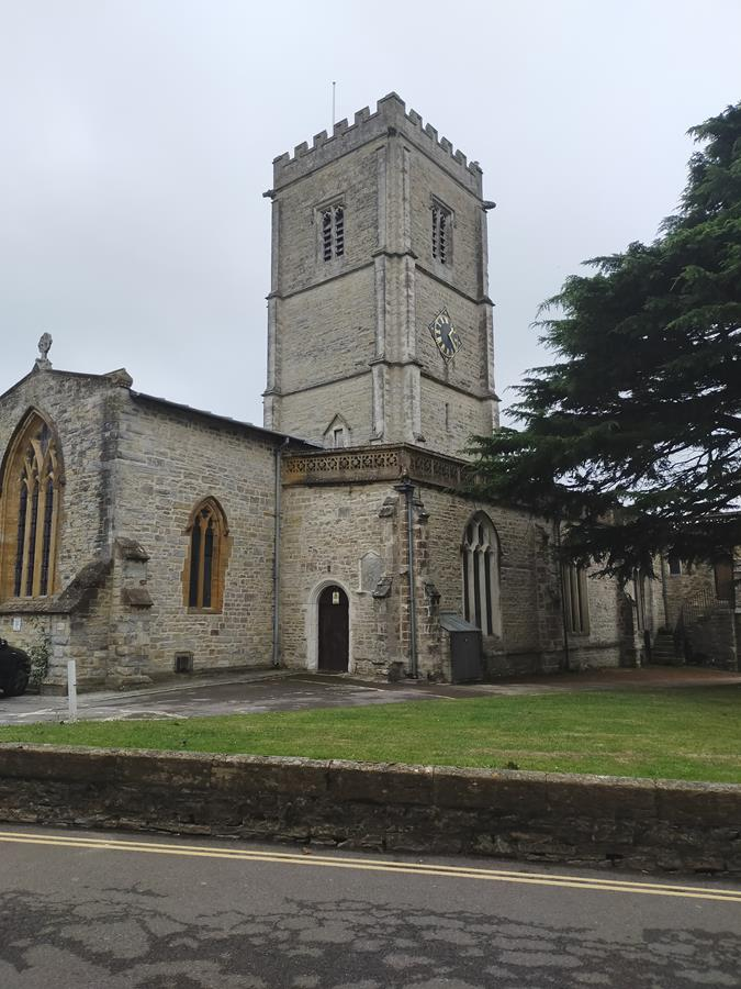 View of St Mary's Church. This is Axminster's parish church and the oldest building in the town. The building has Norman origins, although most of it dates from the 13th to 15th centuries. It has a substantial central stone tower topped with a crenellated parapet.