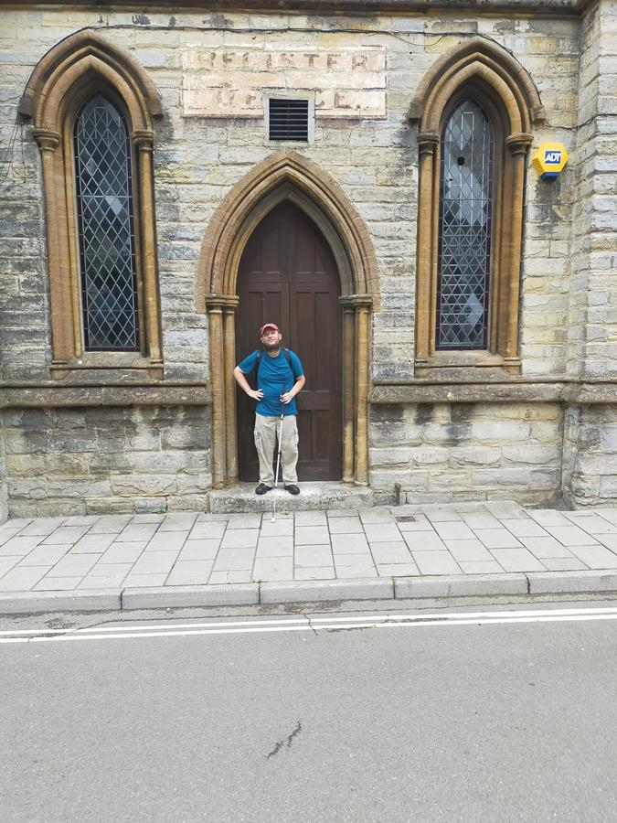 Tony outside the Old Registry Office on Silver Street, Axminster. This narrow two storey stone building dates from the 19th century but looks older. It is Early English Gothic in style with Gothic arches above the door and windows. A faded Register Office sign painted above the door.