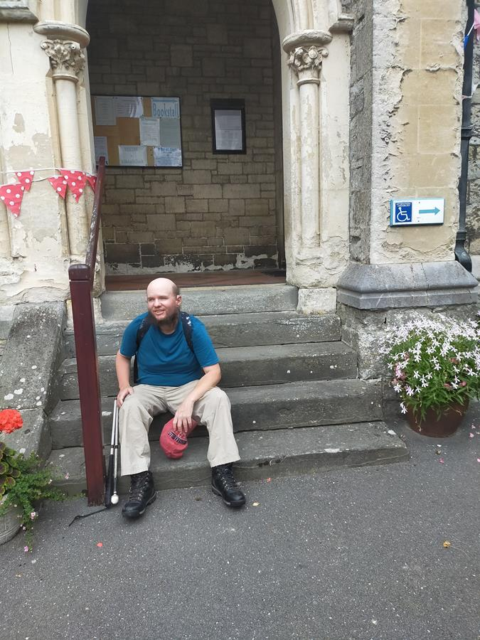 Tony sitting on steps outside the doorway to the parish church of St Michael in Beer, Dorset. This stone church was consecrated in 1878, the present building replacing a 16th century chapel.