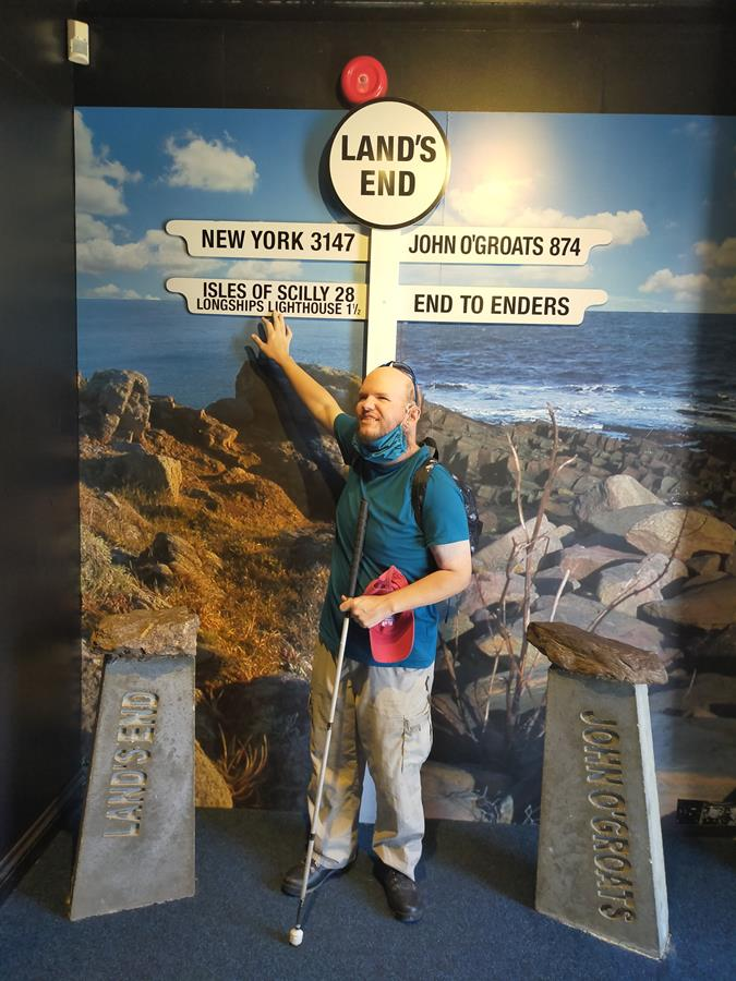 Tony touching a signpost at Land's End: it points to the Isles of Scilly, New York and John O'Groats. This signpost is located indoors with a large printed view of the rocky shore and sea seen from Land's End on the wall behind.