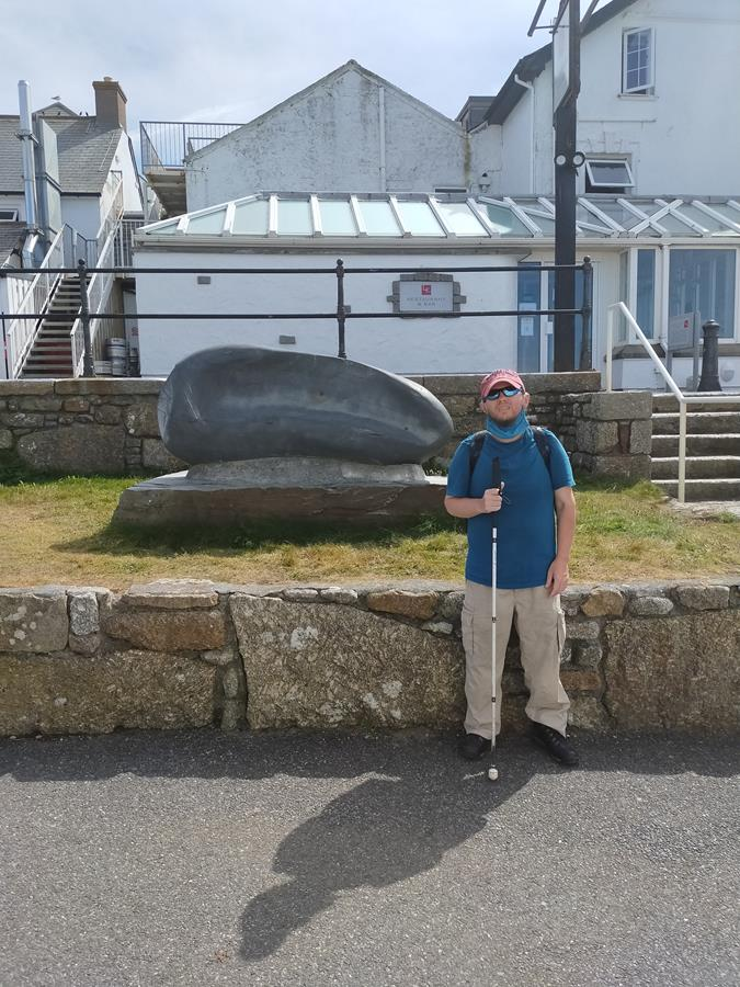 Tony with the Land's End Hotel behind. A stone sculpture called The Gentle Wave by Max Barrett stands on grass in front. In the late 19th century there was a small house at Carn Kez, owned by the First and Last Inn,  where the horses were kept whilst visitors explored the cliffs. This house eventually developed into the present hotel.