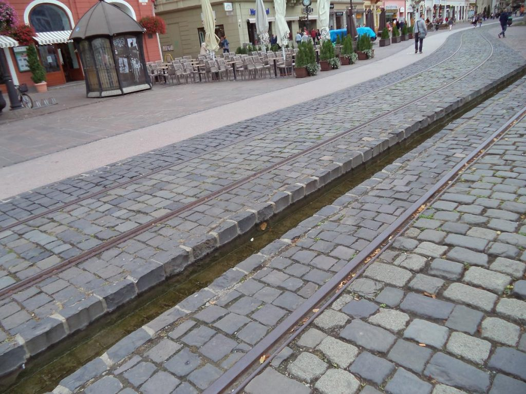 Looking south along Hlavná ulica (Main Street). The middle part of the street is cobbled with a pair of disused tram tracks running either side of a narrow water-filled channel. Hlavná ulica is the principal street and thoroughfare of Košice. Mainly pedestrianised it runs north-south and contains many shops and historical houses, former palaces and churches.