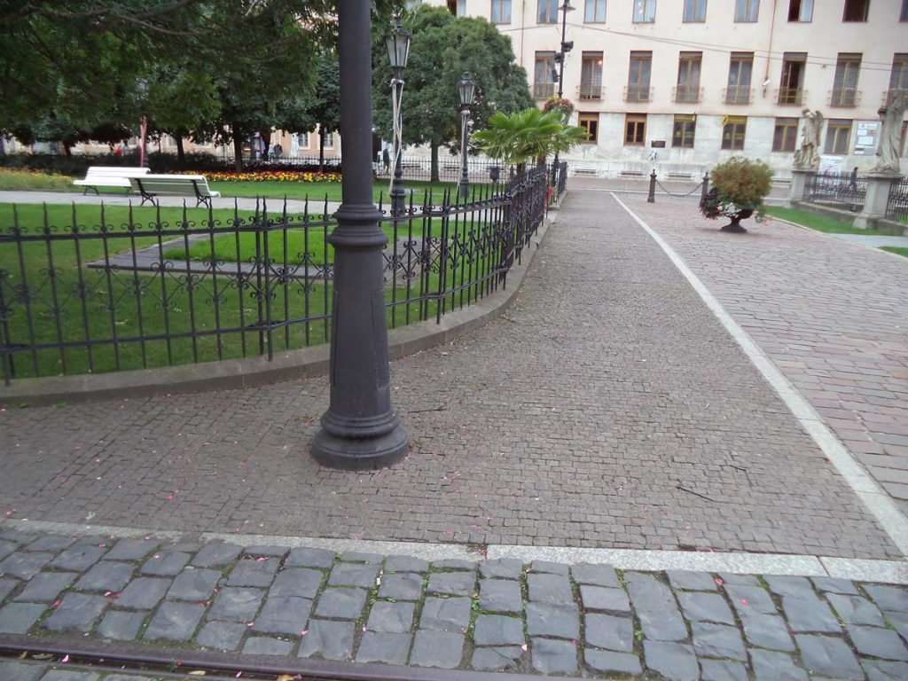 A short cobbled street joining the east and west parts of Hlavná ulica. Either side are small formal parks enclosed by railings. On the right side, the railings are punctuated by a series of statues standing on stone pillars (two are visible). These railings enclose the Plague Pillar or Immaculata (not in view).