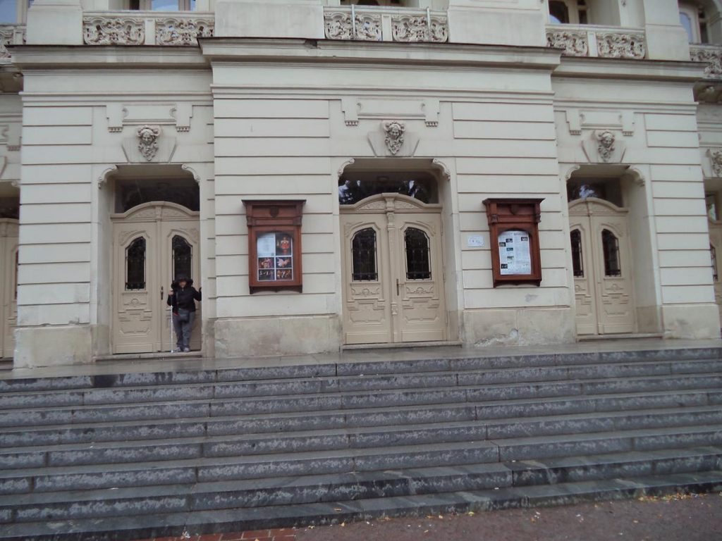 A row of entrance doorways at the north side of the Košice State Theatre with steps in front. Tatiana is standing in one of the doorways.