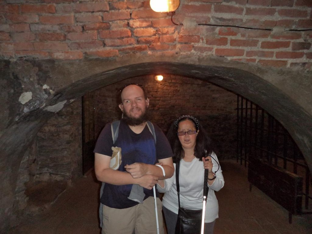 Tony and Tatiana standing under a stone arch inside Mikluš Prison. Metal bars enclosing a cell behind.