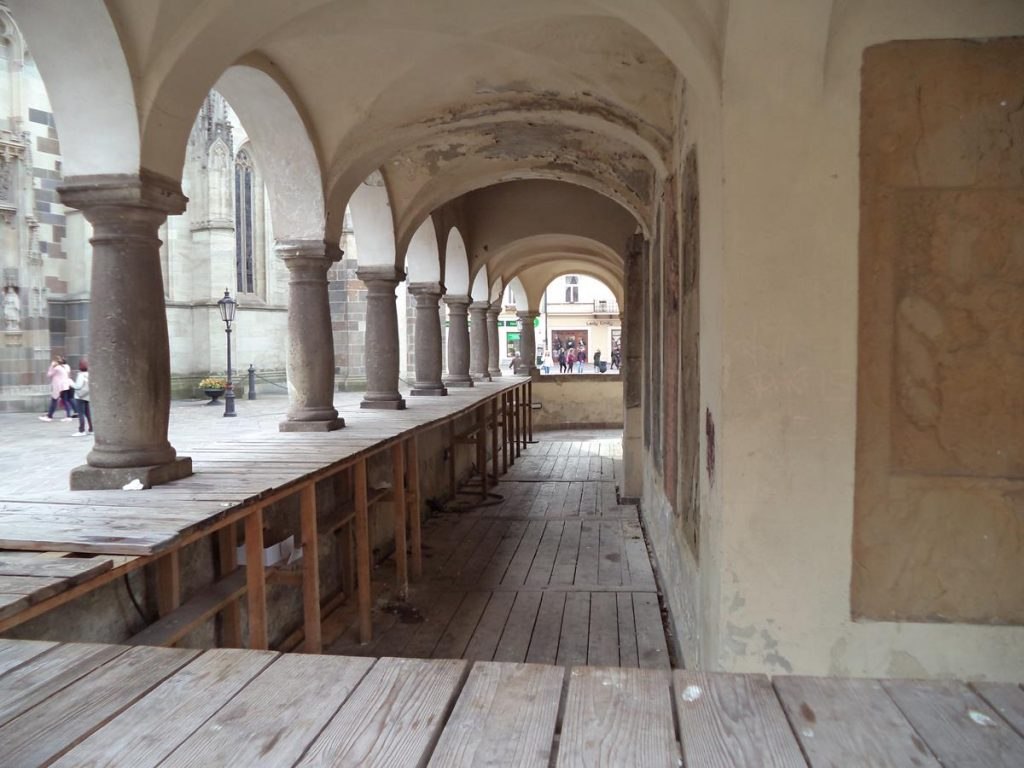 Looking into a colonnade that runs around the base of St Urban Tower. The colonnade is supported by stone columns with a low wall beneath. There is a wooden floor within.