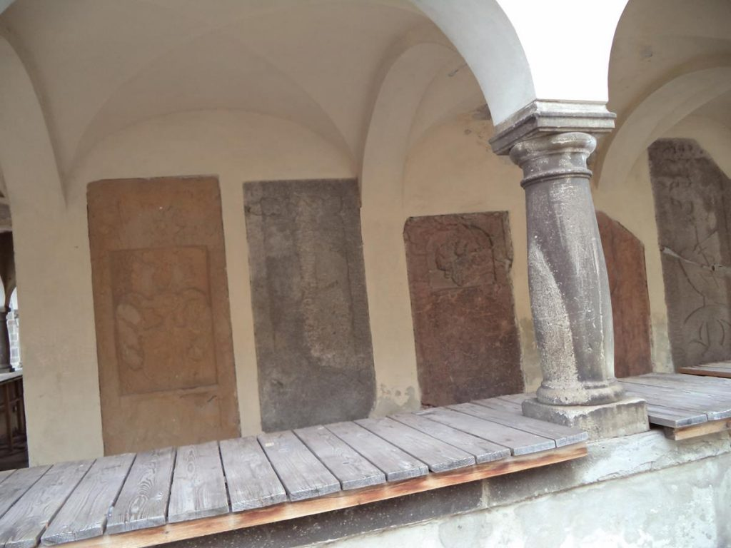 A series of old gravestones embedded in the wall inside the colonnade of St Urban Tower. The stones mostly date from the 14th and 15th centuries.