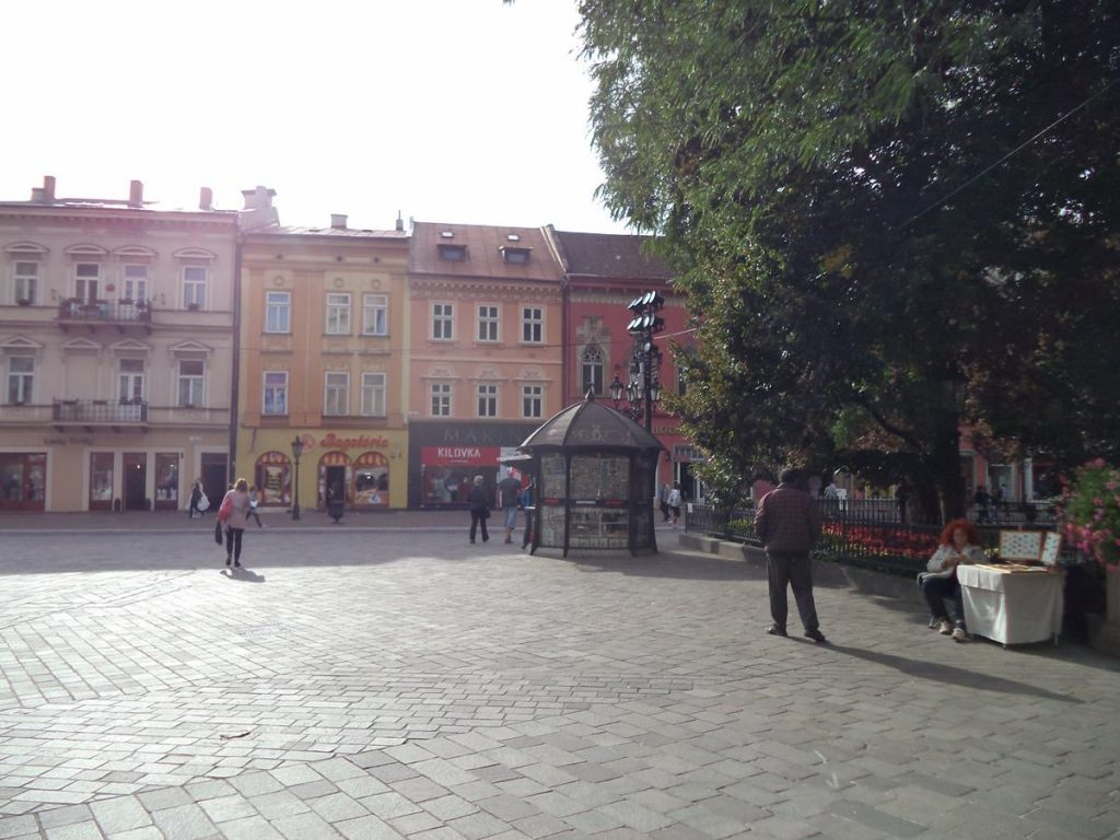 Looking towards old buildings on the west side of Hlavná ulica with the park containing the Singing Fountain on the right and a kiosk in between.
