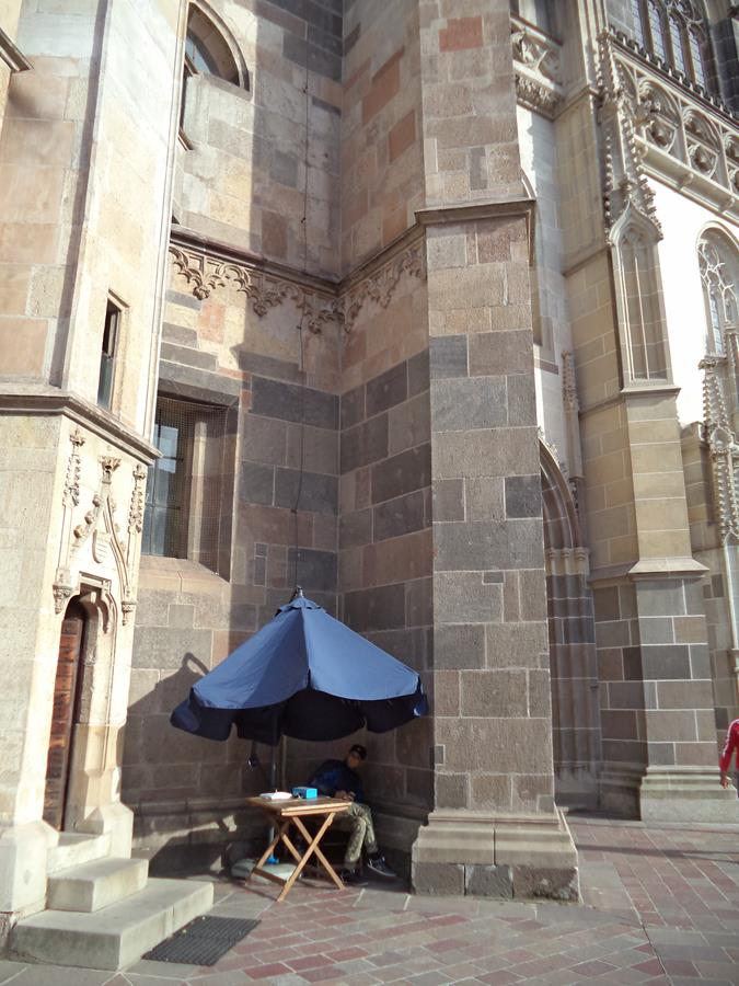 A small side entrance that leads  to Sigismund's Tower, located a few metres from the entrance to St Elisabeth Cathedral. A man sitting under a sun umbrella alongside, selling tickets for Sigismund's Tower.
