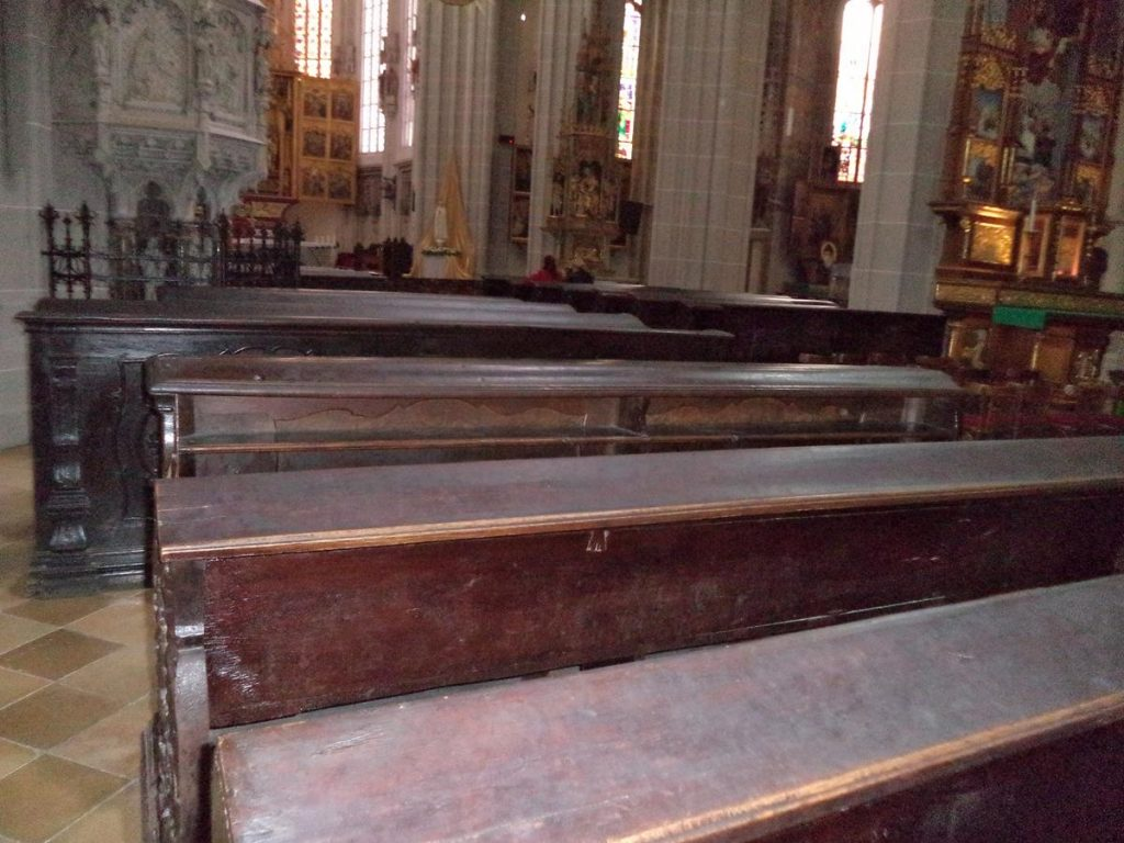 Rows of wooden pews inside St Elisabeth Cathedral with the 15th century main altar just visible in front. Another side altar is part visible on the right and the stone pulpit is to the left.