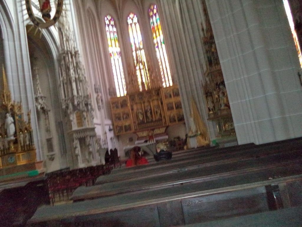 A slightly blurred view of the main altar with stained glass windows above. The altar was crafted in the period between 1474 and 1477. It is golden in colour and contains several paintings and statues. It includes two folding side screens, each containing six Gothic paintings.