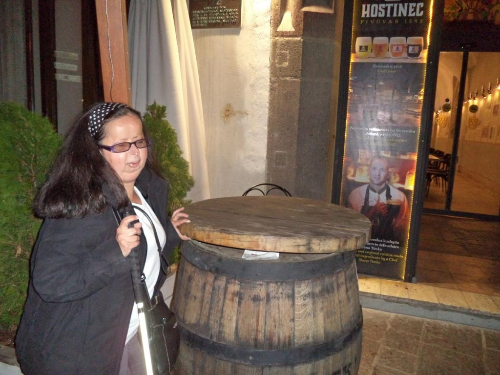 Tatiana next to a wooden barrel outside a restaurant on Hlavná ulica. The barrel may contain beer or wine.