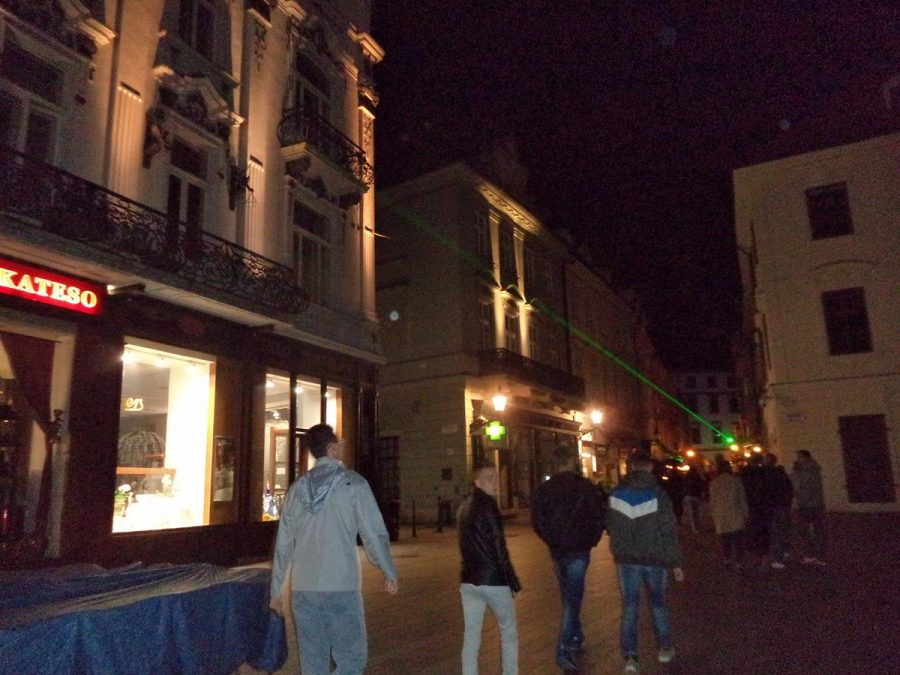 At the south-west corner of Hlavné námestie. People heading along Sedlárska, a street leading into the square, with a green laser beam shining overhead from the far end of the street.