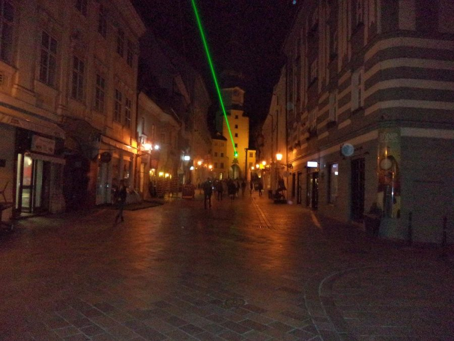 View along Michalská street with Michael's Gate lit up at the far end. Another decorative green laser beam shines overhead from Michael's Gate down the length of the pedestrian street. Michael's Gate is the only preserved gate in the fortified walls of the Old Town. Built in about the year 1300, its present shape is the result of Baroque reconstructions in 1758, when a statue of St Michael and the Dragon was placed on top. The tower above the gate stands at 51 metres high.