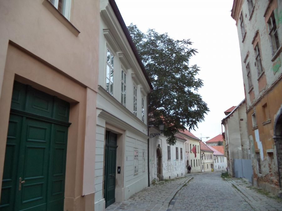 Looking down Kapitulská Street, a cobbled medieval back street on the west side of the old town. Old houses line the street: some of them are derelict and crumbling, while others are restored. This area of the old town feels very old and gives an impression of a town in medieval times.