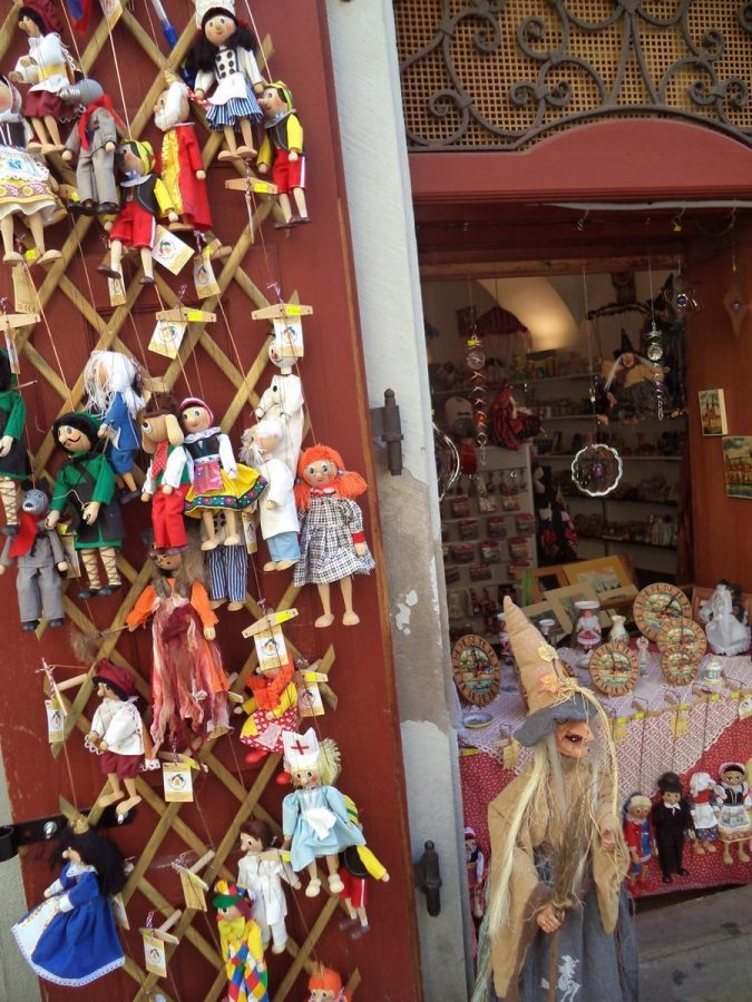 A souvenir shop with a display of marionette string puppets. The puppets are a mixture of human and animal characters. Along side is a larger model of a witch with a pointed hat and holding a broom. This is what can get photographed when pictures are taken by a blind person!