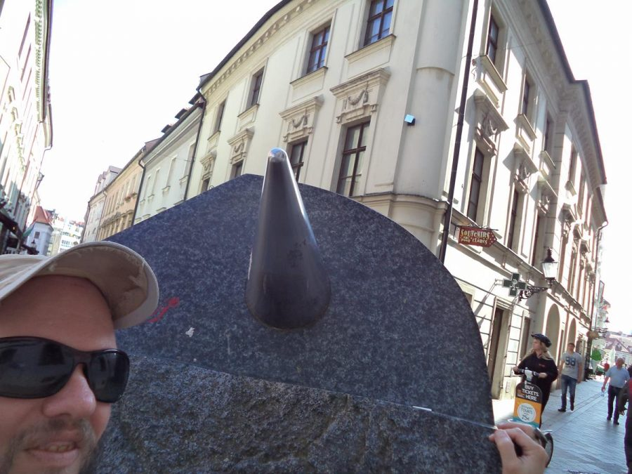 Tony touching an abstract sculpture located on Michalská Street. It is a large irregularly-shaped piece of granite. Parts are rough rock while others are flat and polished. A metal cone is attached to one face. It was created by Slovak sculptor Oto Bachorík in 2003.