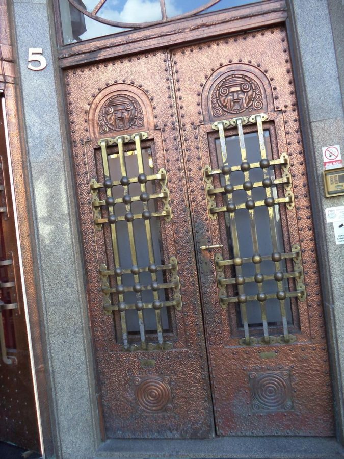 An interesting Art Nouveau metal doorway that belongs to the Palace of the Hungarian Discount and Exchange Bank on Hlavné námestie. A pair of doors with a mixture of angular and curved geometric patterns including two stylised human-like faces above rectangular windows.