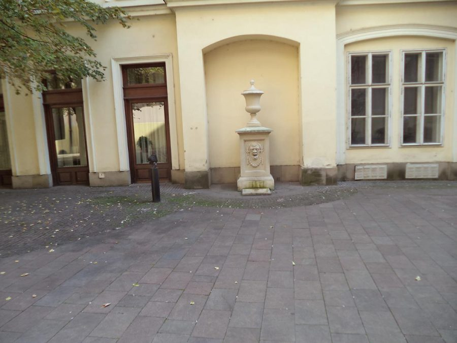 The second courtyard of the Primate's Palace. In front, a decorative stone pillar, topped with an urn inside an alcove.