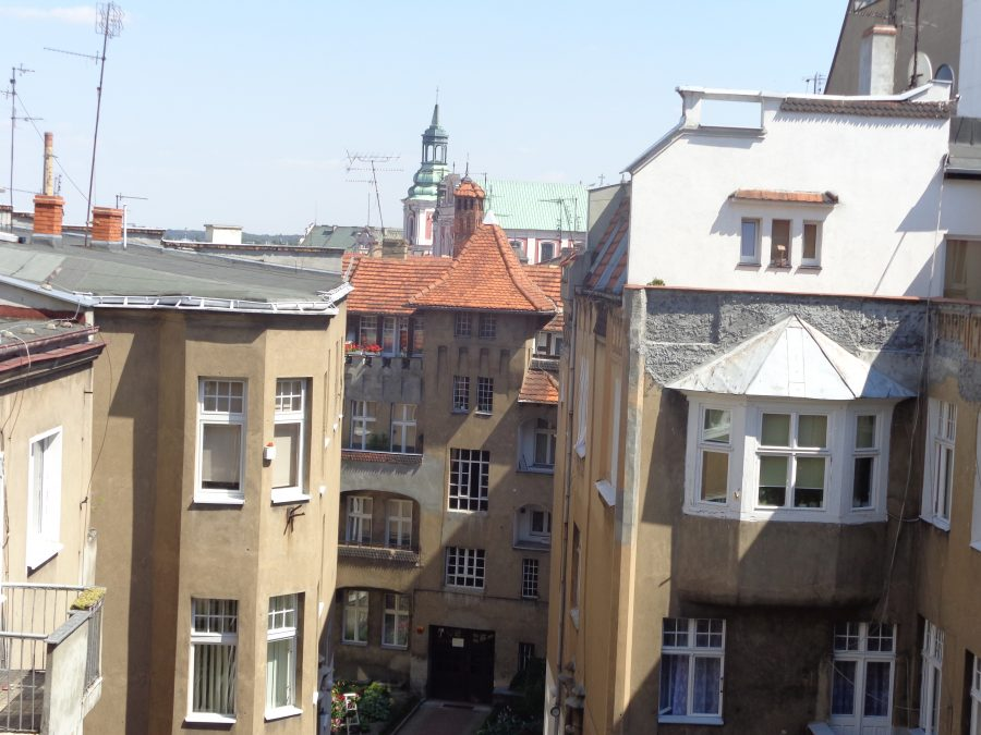 View from an upper storey window or balcony across the roofs of Poznań's historic Old Town neighbourhood, which dates back to 1255. A courtyard down below. In the middle distance, the main tower of Poznań Fara church (also known as St Stanislaus Church). This large church was built between 1651 and 1701 in Baroque style.