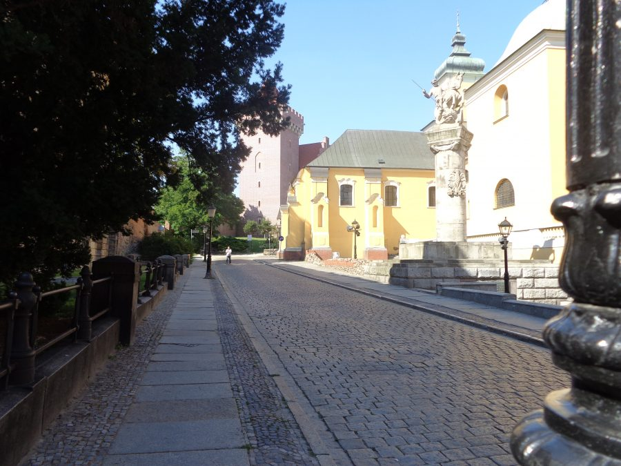 Looking along Ludgardy street on the west side of the Old Town. To the right is the monument to the 15th Poznań Lancers Regiment. This regiment fought the Bolsheviks in 1920 and also during the Second World War as part of the Poznań Army. The original monument was unveiled in 1927, but was later destroyed during the Nazi occupation. A replacement was erected in 1982. The stone monument consists of a stone column topped with a soldier on horseback slaying a dragon using a lance. Further to the right part of the Franciscan Church can be seen. This Baroque church was built between 1674 and 1728. Also in view, away in front, is a crenellated stone tower, part of the 13th century Royal Castle. The castle was largely destroyed during the Second World War but has since been partly rebuilt.