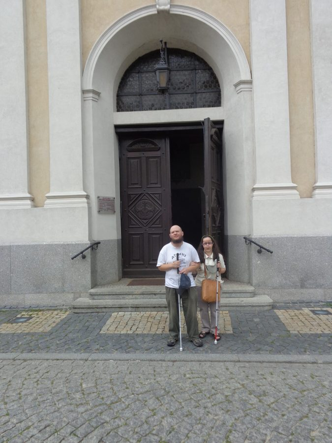 Tony and Tatiana outside another entrance on the south side of Poznań Cathedral. Wooden doors with a white and cream rendered surround.
