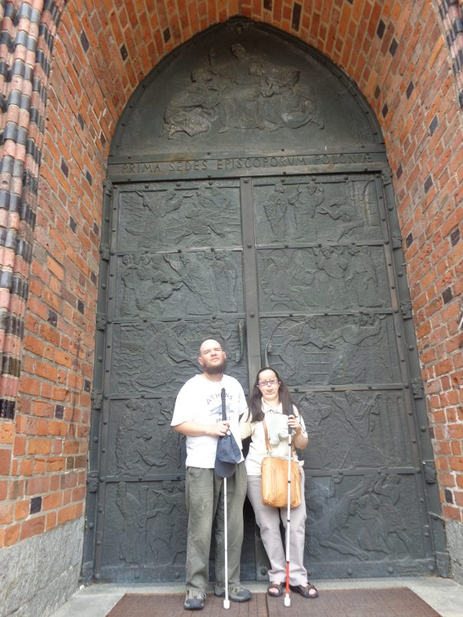 "Tony and Tatiana outside the large main doorway to Poznań Cathedral (officially named the Archcathedral Basilica of St. Peter and St. Paul). The pair of metal doors are embossed with Biblical scenes. The cathedral is located on Ostrów Tunski ""Cathedral Island"", north-east of the city centre, and the location of the city's original settlement."