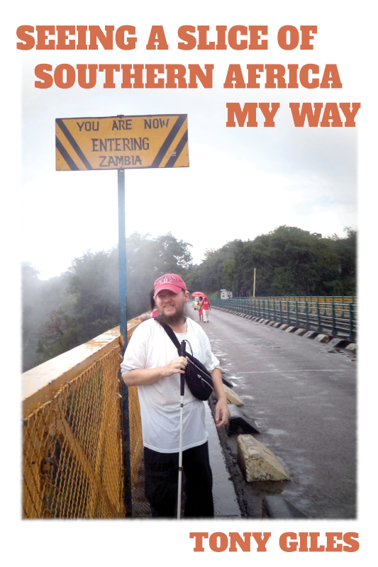 Seeing a Slice of Southern Africa My Way book cover.  The cover shows Tony on Victoria Falls Bridge crossing the misty Zambezi River on the border between Zimbabwe and Zambia. A sign reads 'You are now entering Zambia'.
