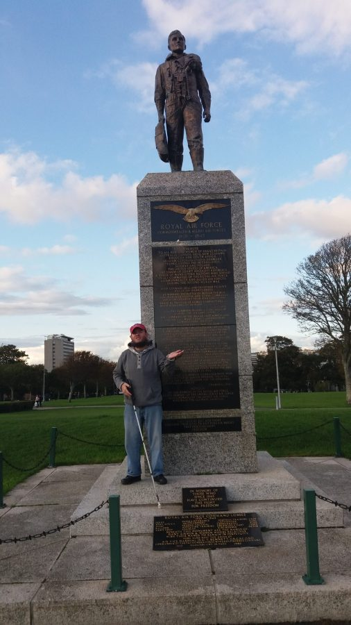 Tony in front of the RAF and Allied Air Force Monument, erected in 1989. The monument consists of a stone plinth with a sculpture of an unknown airman standing on top. The airman is looking out to sea and is holding a parachute in his right hand.