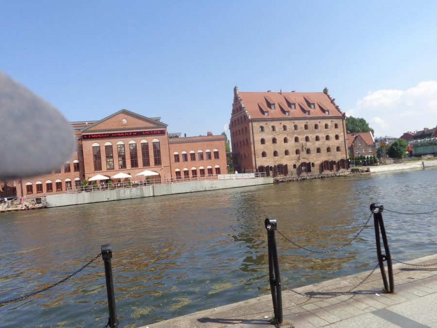 View across the Motława river with two prominent buildings on the opposite bank. On the left is the Polish Baltic Philharmonic, a concert hall, which is housed in a former power station. It was constructed in 1897-1898 with a brick neo-Gothic facade. It closed as a power station in 1996. On the right, a historic granary dating from the 17th-century, and now converted into a hotel. It is built of brick with lots of small windows. These buildings are located on the island of Ołowianka, which is formed by the Motława river and the Stepka channel.