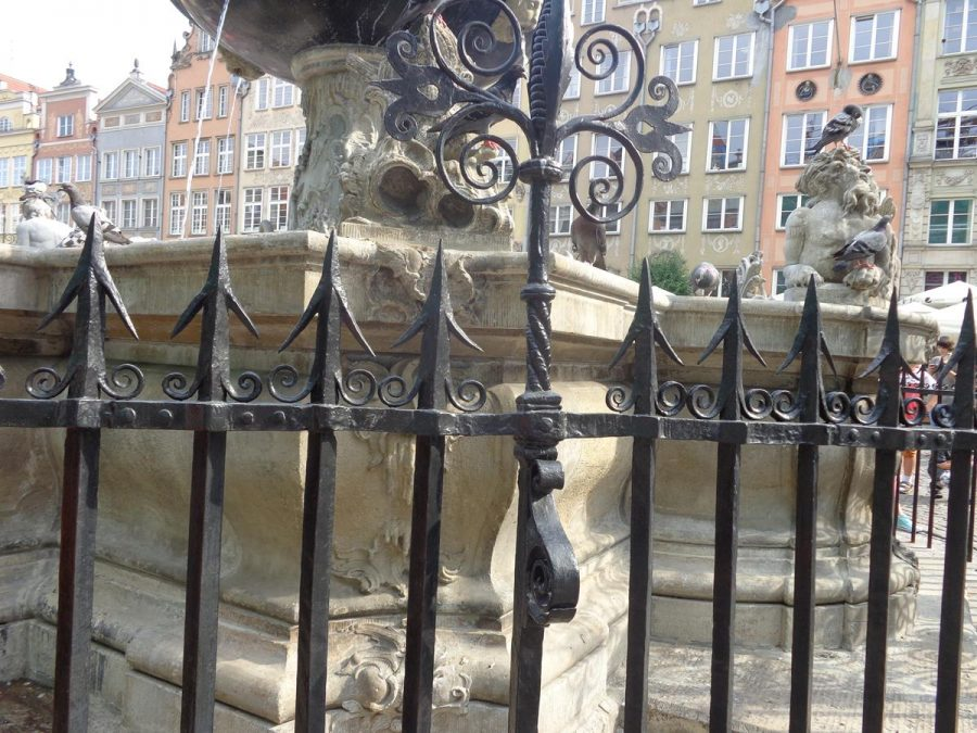The lower stone part of Neptune's Fountain located in Long Market (Długi Targ) with surrounding metal railings. Constructed around 1633, this Mannerist-Rococo fountain is one of the city's main landmarks. The stone base was designed by Abraham van den Blocke while the bronze figure of Neptune is by sculptors Peter Husen and Johann Rogge.